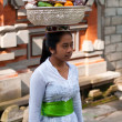 Balinese Woman Carrying Offerings On Her Head - Stock Photo