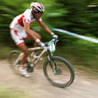 Stock Photo: Sportsman's on white bike motion photo