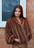 Portrait of luxurious young woman in a fur coat — Stock Photo
