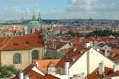 St. Nicholas Church and the red roofs in Prague — Stock Photo