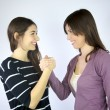 Two girlfriends holding hands smiling laughing — Stock Photo