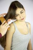 Brunette female model getting hair brushed by hairdresser — Stock Photo