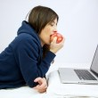 Woman eating red apple in front of computer laying in bed — Stock Photo