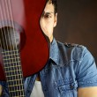 Male model hiding behind guitar — Stock Photo