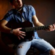Serious male model with guitar intense - Stock Photo
