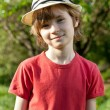 The fair-haired boy in red shirt and hat - Stock Photo