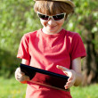 Joyful boy plays in the Tablet PC - Stock Photo