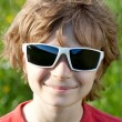 Stock Photo: Blonde naughty little boy wearing sunglasses