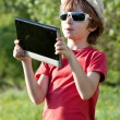 Stock Photo: Fair-haired boy plays in Tablet PC