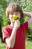 Teenager enjoys odors from dandelions — Stock Photo