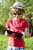 Joyful boy plays in the Tablet PC — Stock Photo