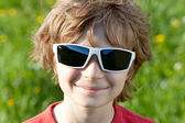 Blonde naughty little boy wearing sunglasses — Stock Photo