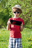 The fair-haired boy in a hat with a computer — Stock Photo