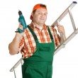 Worker, dressed in overalls with a drill aluminum ladder — Stock Photo