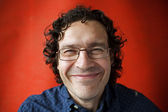 Shaggy and unshaven smiling man with glasses — Stock Photo