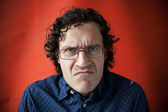 Man wearing glasses with a grimace of displeasure — Stock Photo