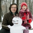 Dad and daughter next to snowman — Zdjęcie stockowe #8443858