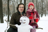 Dad and daughter next to the snowman — Stock Photo
