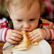 Stock Photo: Baby eats delicious pancakes