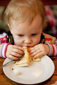 Baby eats the delicious pancakes — Stock Photo