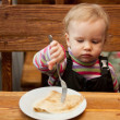 Stock Photo: Blond little girl eats pancakes