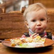Blond little girl in front of a big plate — Stock Photo #8604481
