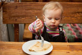 Blond little girl eats pancakes — Stock Photo