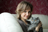 Pretty young woman playing with a gray cat — Stock Photo