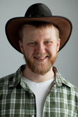 The good-natured cowboy hat and a green plaid shirt — Stock Photo