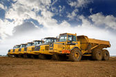 Row of yellow heavy tipper lorries — Stock Photo