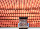 Red roof tiles with chimney — Stock Photo