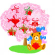 Painted teddy bear under blossoming  tree — Stock Photo