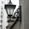 Lamp on fence wall — Stock Photo