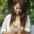Happy Asian girl using tablet pc outdoor — Stock Photo