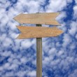 Foto de Stock  : Blank wooden arrow sign post against blue sky