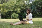 Azjatyckie dziewczyny za pomocą laptopa na trawie — Zdjęcie stockowe