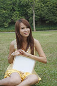 Young Asian girl holding a white board sitting on grass — Stock Photo