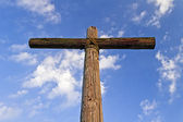A rugged wooden Cross and blue, cloudy sky — Stock Photo