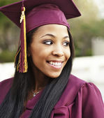 Happy woman in graduation cap and gown — Stock Photo