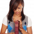 Young Woman Praying while holding a bible — Stock Photo