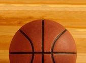 Basketball on floor of hard wood court — Stock Photo