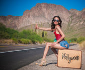 Young woman hitching a ride on lonely desert road — Stock Photo