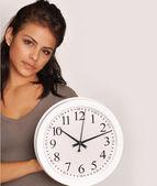 Mladá žena drží hodiny. — Stock fotografie
