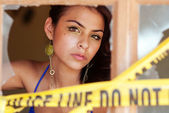 Woman peeking out of window crime scene — Stock Photo