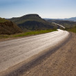 Asphalt road turn in a sunny valley — Stock Photo