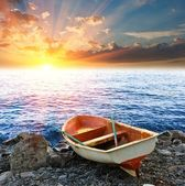 Touristic boat on a coast by a sunset — Stock Photo