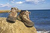 Turistické boty na pobřeží moře — Stock fotografie