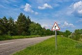 Sign on asphalt rural road — Stock Photo