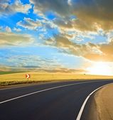 Asphalt road turn at the sunset — Stock Photo