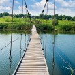 Wooden bridge across rural river — Stock Photo #8063810